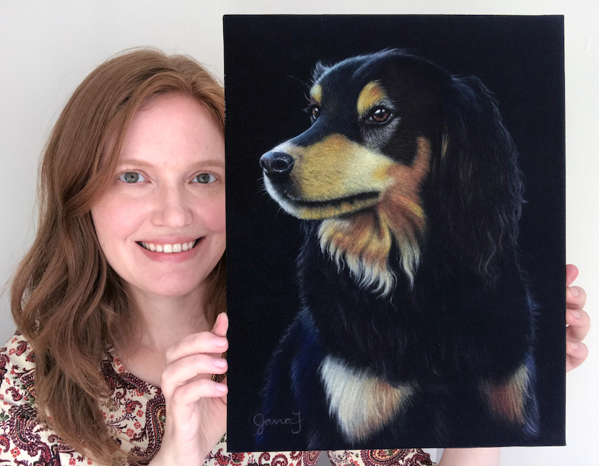 Redheaded woman holding a painting of a dog